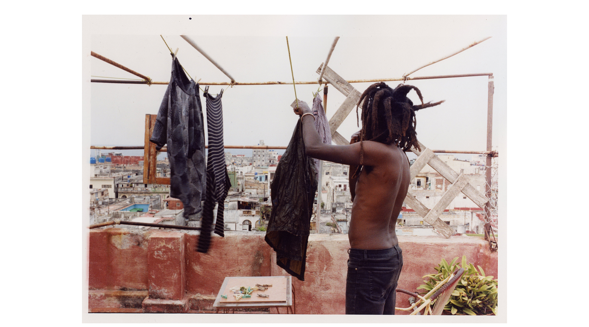 a man hangs out his washing on a rooftop overlooking mexico city