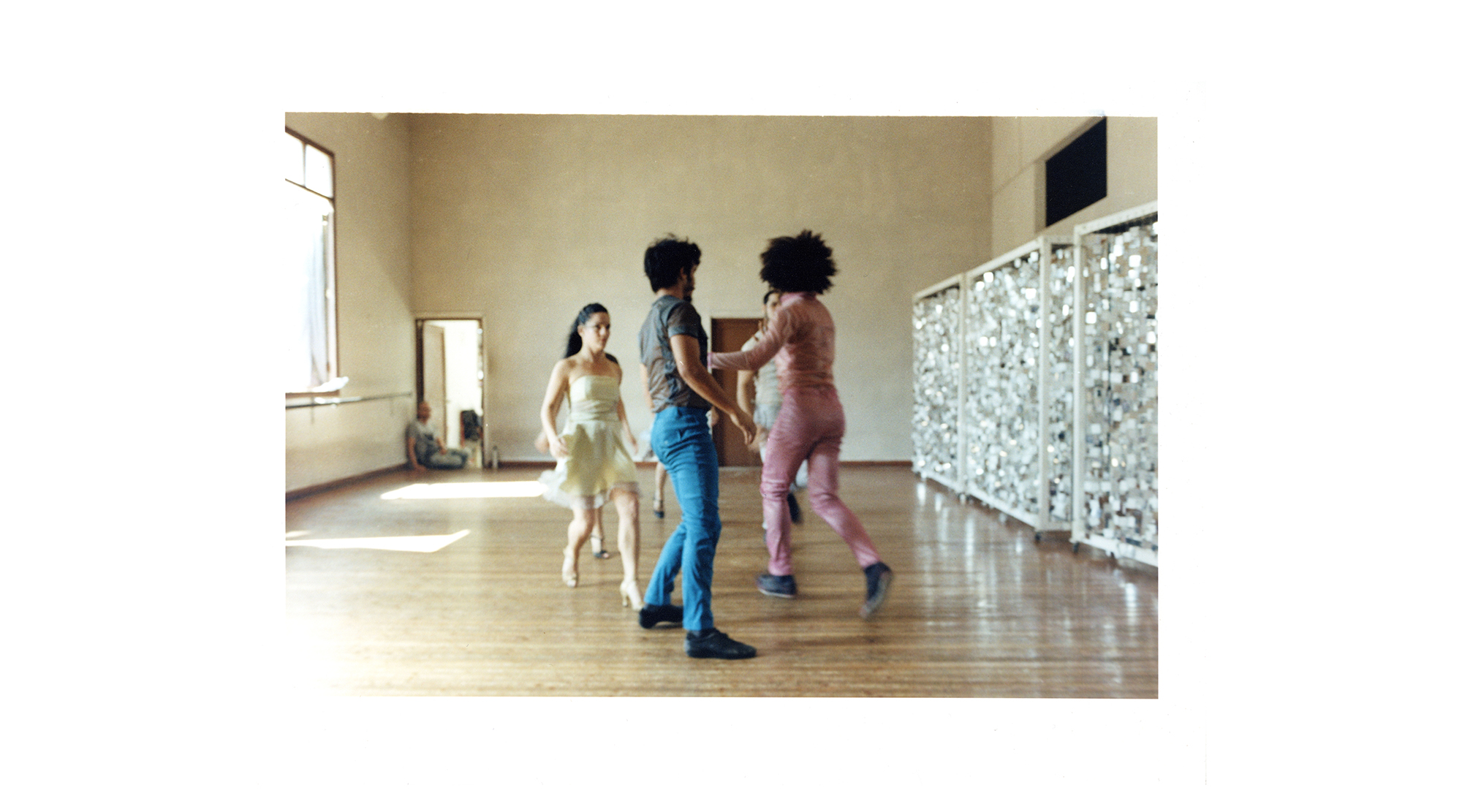 five dancers in colourful clothes dance in a sunny studio