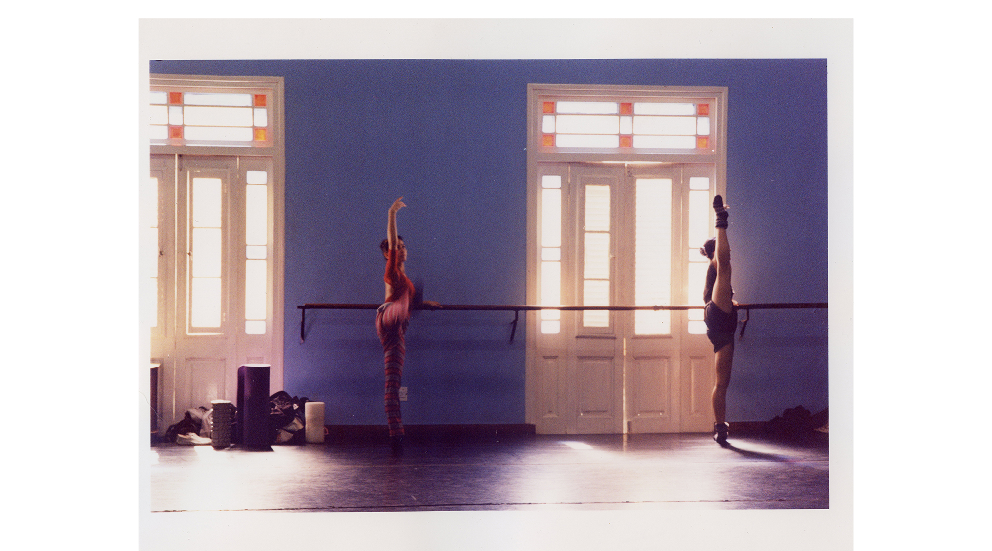two dancers stretch at a ballet barre by a bright window