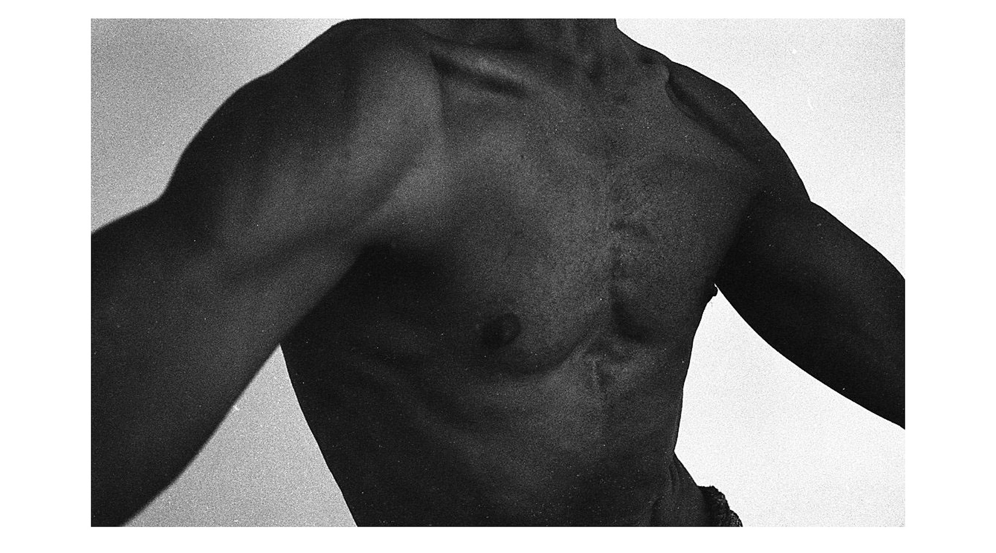 a black-and-white close up of a muscular male torso