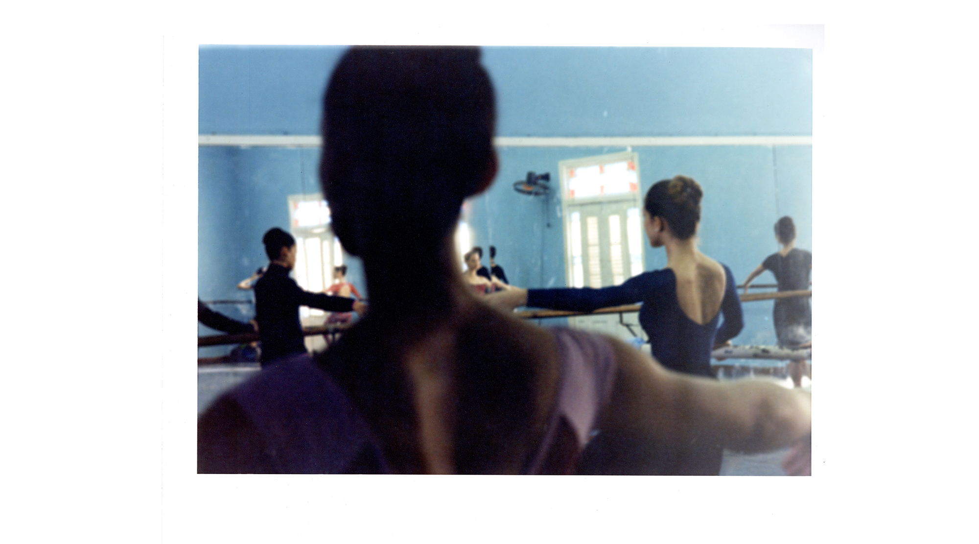 a photograph, shot from behind a dancer's head, captures a busy rehearsal room