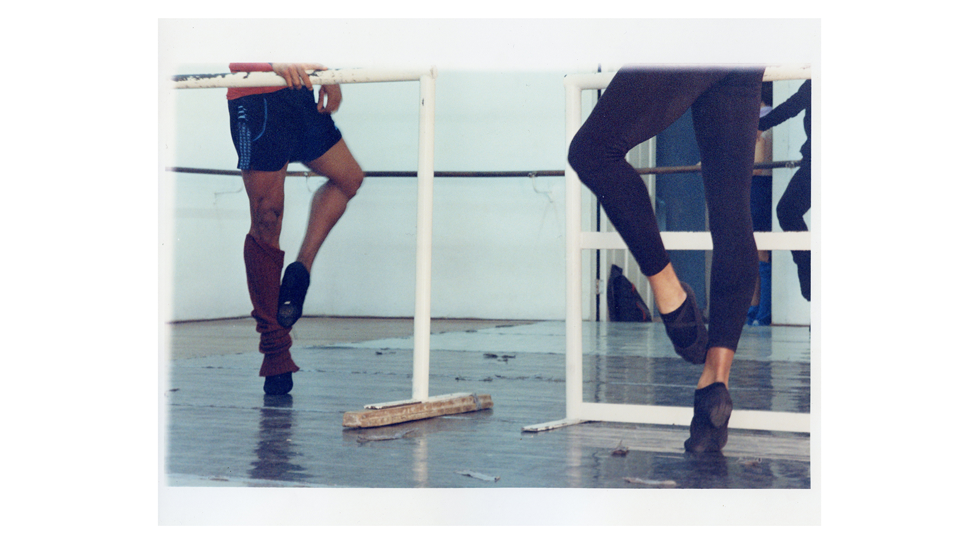 the lower bodies of two dancers standing by ballet barres
