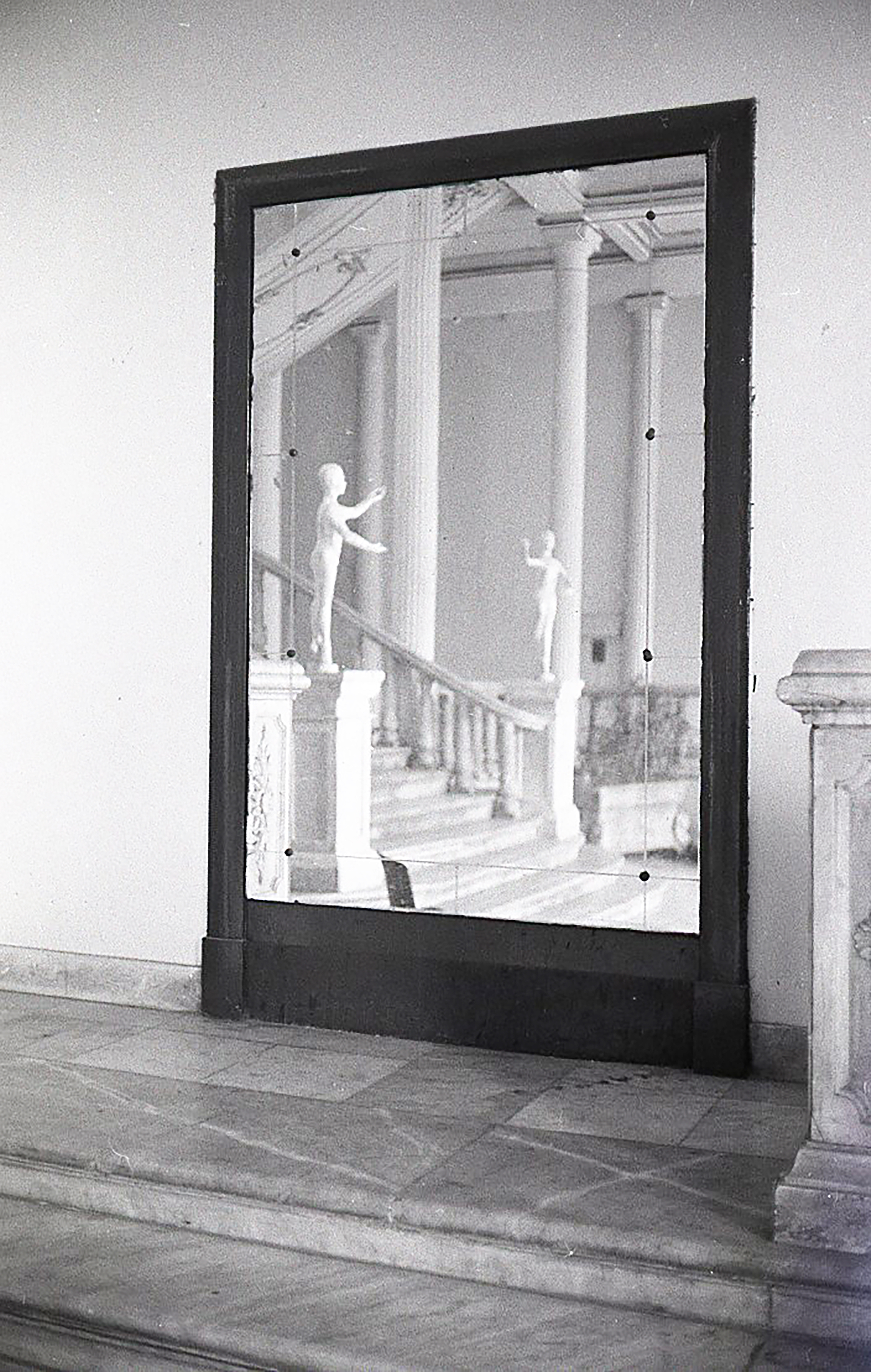 a mirror reflection showing a lavish marble hallway and staircase